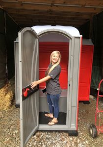 girl stepping out of Portable toilet